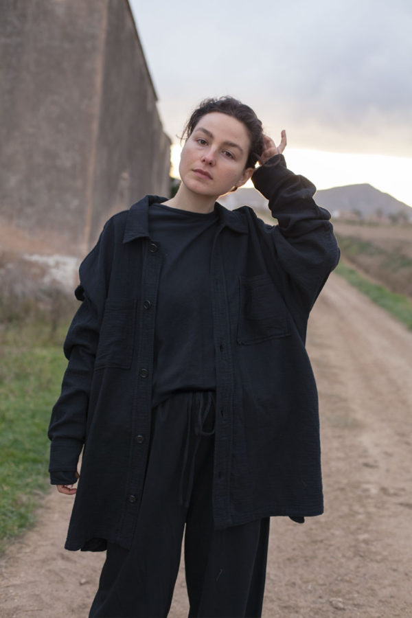 model is wearing the unisex levi overshirt paired with the oli top and pants all in black color