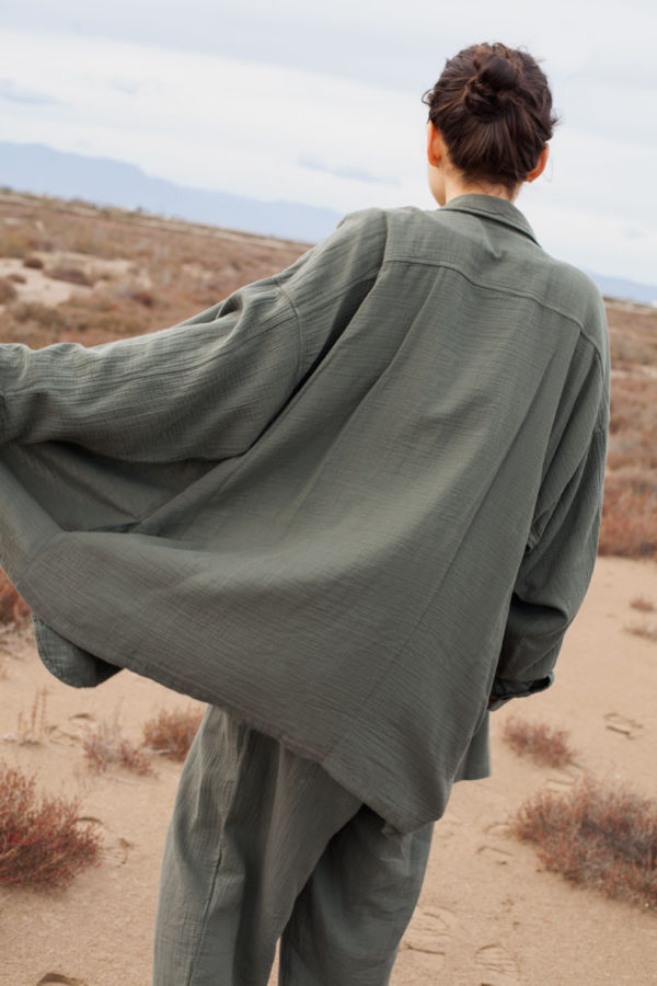 backview of model wearing the unisex levi overshirt paired with the oli pants both in olive color