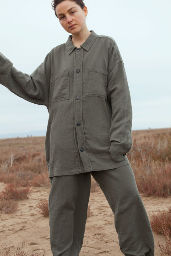 model is wearing the unisex levi overshirt paired with the oli pants both in olive color