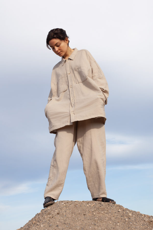 model is wearing the unisex levi overshirt paired with the oli pants both in stone color
