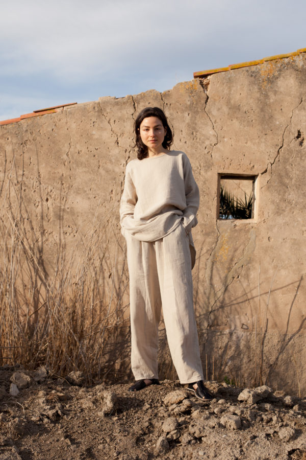 model is wearing the oli top in organic cotton paired with the oli pants in organic cotton both in stone color