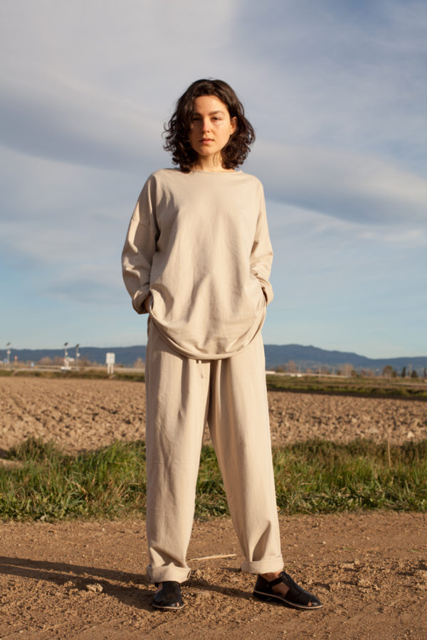 model is wearing the pina sweatshirt paired with the pina pants both in stone color